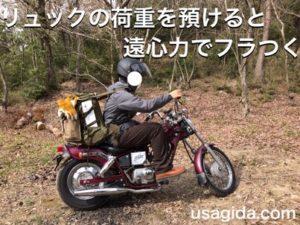 肩紐をゆるめたリュックを背負ってバイクに跨っている男