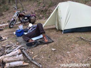 テントの前に敷かれたマットで横になる男