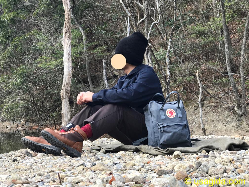 ダナーフィールドを履いて河原に座る人